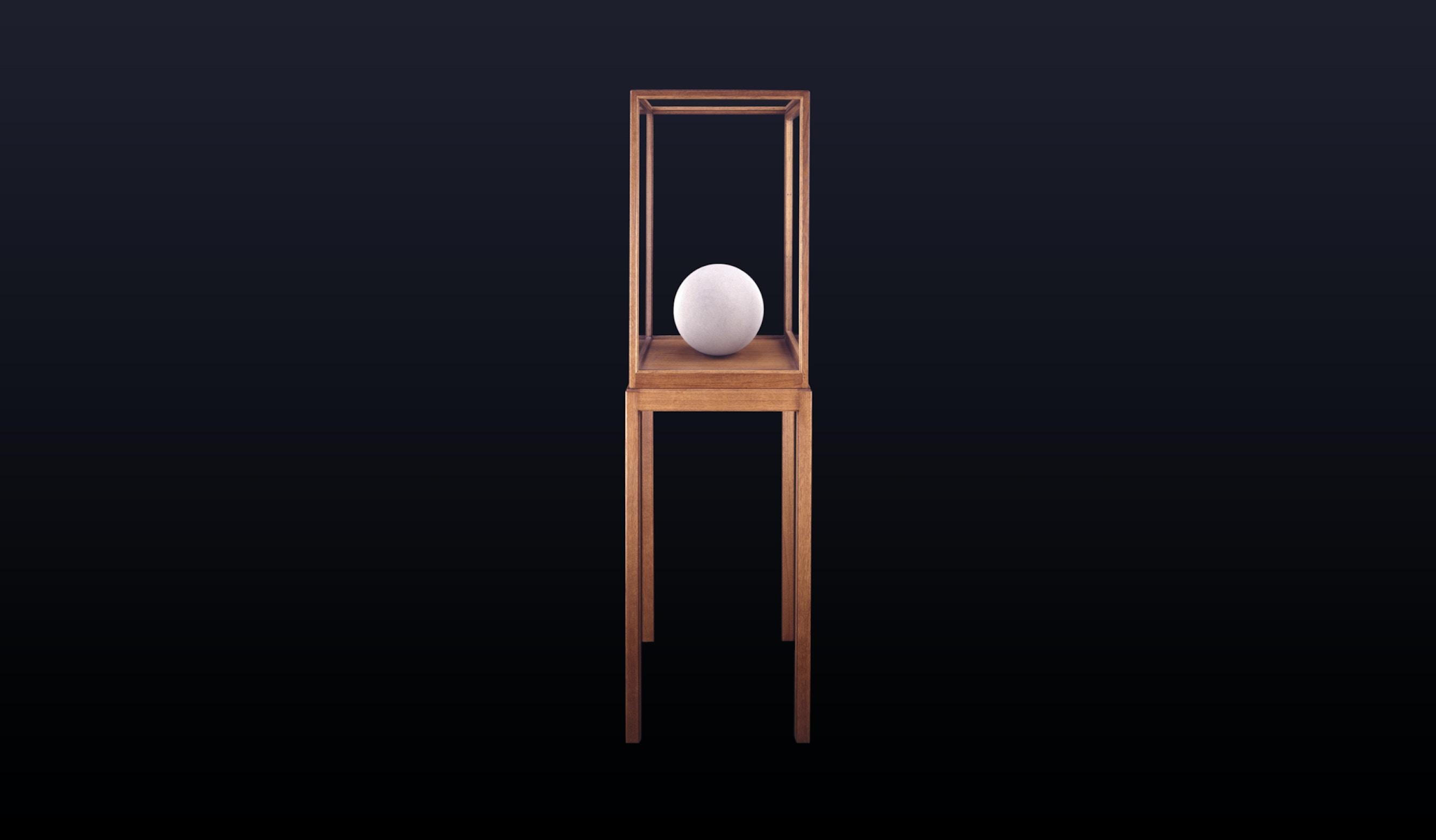 En rund skulptur som står inne i et trekabinett med bein