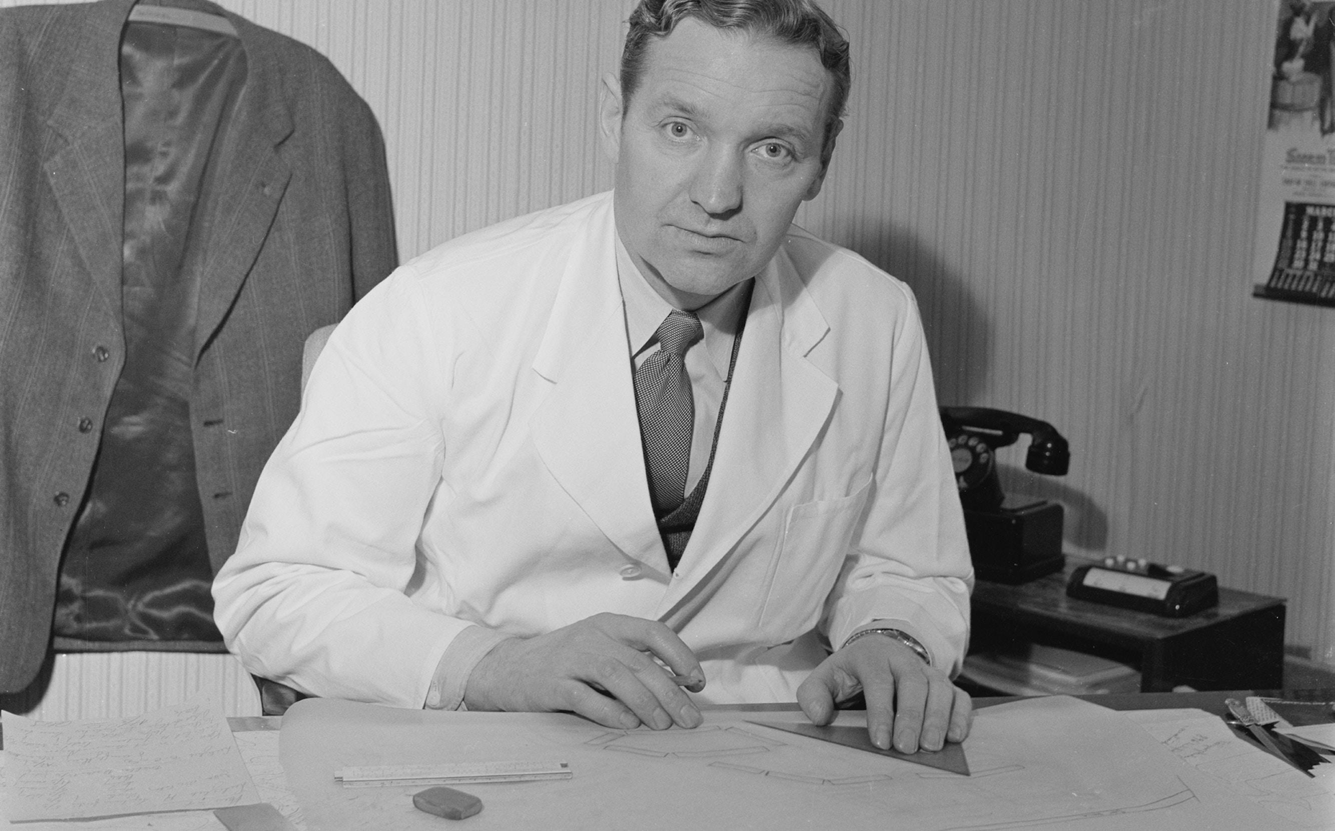 Fotografi av gamle Olav Selvaag bak arbeidspulten