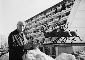 Portett av Olav Selvaag foran skulpturer og boligblokk